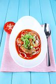 Fresh prawns with spaghetti and lettuce in tomato sauce in a white oval bowl on a napkin on blue wooden background