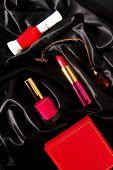 lipstick and nail polish on black fabric