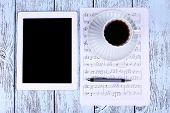 Tablet, cup of coffee printed music and earphones on wooden background