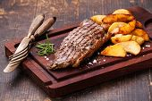 Well Done Grilled New York Steak With Roasted Potato Wedges On Cutting Board On Dark Wooden Backgrou