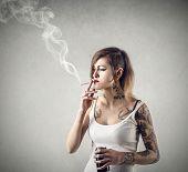 Tattooed girl smoking a cigarette