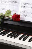 Piano con partituras y una rosa