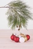 Pine Tree Branch With Red, Whte And Gold Christmas Baubles