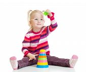 Funny kid in eyeglasses playing colorful pyramid toy isolated on white