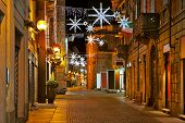 Evening view of cobblestone street in old town of Alba with illuminations and decorations for Christmas and New Year celebrations in Piedmont, Northern Italy.