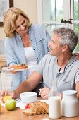 Smiling Woman Serves Breakfast To Her Husband In Morning