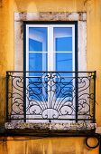 Old and damaged window with iron balcony in a yellow wall