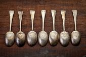 a row of vintage silver tablespoons with patina and scratches against grunge wood background