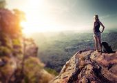 Hiker with backpack standing on top of the mountain and enjoying valley view at sunrise. Edges are blurred