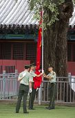 Law Enforcement Officers Raising The Chinese Flag