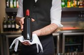 Handsome waiter holding a bottle of red wine in a bar