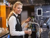 Barmaid pulling a glass of beer while looking at camera in a bar