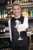 Pretty woman offering flute of champagne in a bar