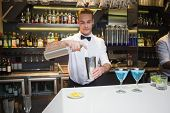 Smiling bartender preparing a drink at bar counter in a bar
