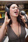 Woman singing with her hands on her headphone at the nightclub
