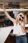 Woman in sunglasses singing and dancing with hand up at the nightclub