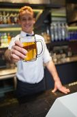 Smiling bartender offering pint of beer to camera in a bar