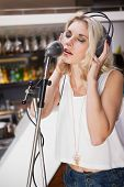 Pretty blonde with headphone singing into microphone at the nightclub