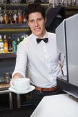 Young barista offering cup of coffee smiling at camera in a cafe