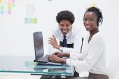 Smiling business coworkers using laptop in the office