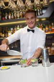Happy bartender making a cocktail in a bar