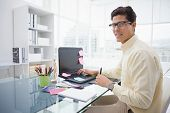 Designer using laptop and smiling at camera in his office