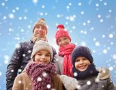 family, childhood, season and people concept - happy family in winter clothes over blue snowy background