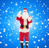 christmas, holidays, gesture and people concept - man in costume of santa claus with bag pointing finger up over blue snowy background