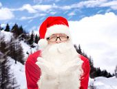 christmas, holidays and people concept - man in costume of santa claus blowing on palms over snowy mountains