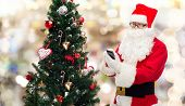 holidays, technology and people concept - man in costume of santa claus with smartphone, presents and christmas tree over lights background