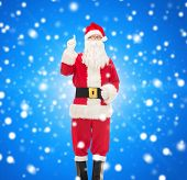 christmas, holidays, gesture and people concept - man in costume of santa claus pointing finger up over blue snowy background