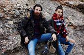 Couple of hipster guys sitting on rock taking break during hike