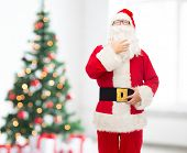 christmas, holidays and people concept - man in costume of santa claus over living room and tree background