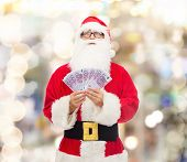 christmas, holidays, winning, currency and people concept - man in costume of santa claus with euro money over lights background
