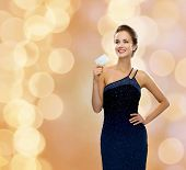 shopping, wealth, holidays and people concept  - smiling woman in evening dress holding credit card over beige lights background
