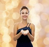 people, holidays and glamour concept - smiling woman in evening dress with diamond over beige lights background