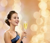 party, drinks, holidays, luxury and celebration concept - smiling woman in evening dress with glass of sparkling wine over beige lights background