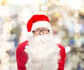 christmas, holidays and people concept - man in costume of santa claus blowing on palms over lights background
