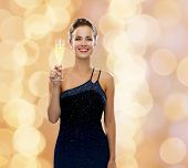 party, drinks, holidays, people and celebration concept - smiling woman in evening dress with glass of sparkling wine over beige lights background
