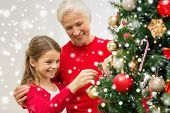 family, holidays, generation and people concept - smiling girl with grandmother decorating christmas tree at home