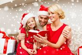 family, christmas and people concept - smiling family in santa hats reading book or bible at home