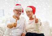 family, holidays, christmas, age and people concept - happy senior couple in santa helper hats sitting on sofa and showing thumbs up gesture at home