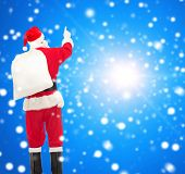 christmas, holidays and people concept - man in costume of santa claus with bag pointing finger from back over blue snowy background