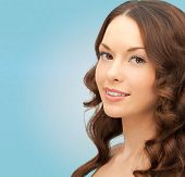 people and beauty concept - beautiful smiling young woman over blue background