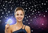 shopping, christmas holidays, money, luxury and people concept - smiling woman in evening dress holding credit card over night lights and snow background