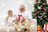 family, holidays, generation, christmas and people concept - smiling grandfather and grandson with gift box sitting on couch at home