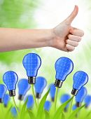 Hand with thumb up and eco energy bulbs. Green energy concept