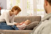 Happy young mother kneeling on sofa, playing with lying baby. Side view,