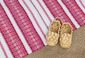stock photo of baste  - A pair of bast shoes on a canvas background - JPG
