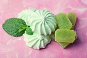 Mint color meringues and candies on color background